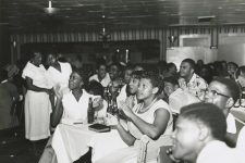 Women clap along with a show at the Dew Drop Inn.