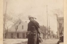An elder African American woman walks through Congo Square