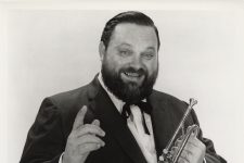 Publicity photo of Al Hirt holding trumpet in one hand and pointing with the other
