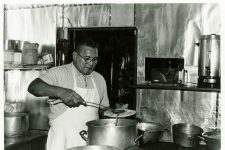 Buster Holmes in a kitchen ladling food onto a plate. The Longshoremen's Recreation Center was located at 2700 S. Claiborne Avenue.