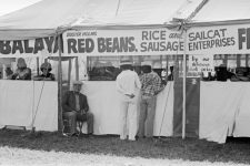 Buster holmes seated in front of a festival vending area