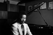 Portrait of Allen Toussaint (b. 1938) sitting with his legs crossed on a piano bench facing away from the instrument. He is seen wearing a light-colored suit, collared shirt, and dark-colored tie, with a large circular pendant necklace hanging in front of his tie and a bracelet on his right wrist.