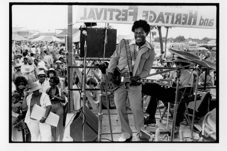 View of Earl King (1934-2003) performing at the 1975 New Orleans Jazz and Heritage Festival. He is seen playing guitar on an outdoor stage while an unidentified musician sits on a keyboard behind him. Earl King performed on Saturday, April 26 at 2 p.m. on Stage 1.