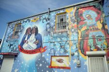 Artist Daniel Fuselier painted several murals on the Lounge, each covering his previous work. This iteration, in 2013, features Ernie K-Doe as the Emperor of the Universe with a Mardi Gras Indian to the right.