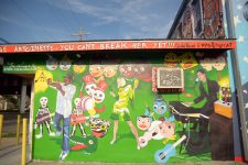 Artist Daniel Fuselier painted several murals on the Lounge, each covering his previous work. This iteration, in 2013, features Quintron and Miss Pussycat, artists who were close to the K-Does. Kermit Ruffins, who took ownership of the club after Antoinette K-Doe's passing, plays trumpet at left.