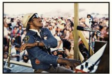 Professor Longhair (1918-1980) performing on an outdoor stage at the 1977 New Orleans Jazz and Heritage Festival. He is seen with his arm raised in the air and a microphone in front of him. A crowd is seen behind him. Professor Longhair performed on Sunday, April 17 at 5:30 p.m. on Stage 1.