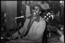 Tommy Ridgley (1925-1999) performing at the Professor Longhair Fire Benefit. He is seen playing piano and singing into a microphone while wearing sunglasses, a dark-colored collared shirt and a checkered blazer. From the Times Picayune, April 16, 1974: