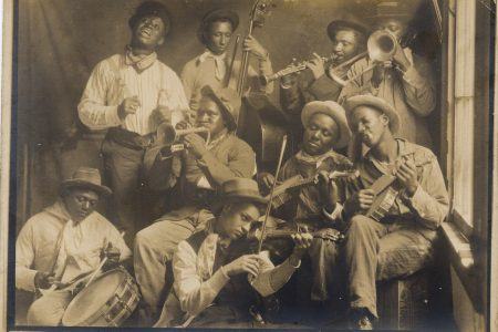 "Shown from left to right are Clarence Williams; John Lindsay with bass; Jimmie Noone with clarinet; William ""Bebe"" Ridgley with trombone; Ernest Trepagnier with snare drum; Oscar Celestin with cornet; Armand J. Piron with violin; Tom Benton with banjo; and Johnny St. Cyr with banjo."