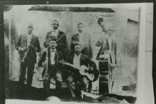 Negative of the only photo of Buddy Bolden, who is standing next to the string bass.
