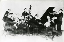 "From Chicago in 1926, Jelly Roll Morton at the piano with his band: Andrew Hillaire, Edward ""Kid"" Ory, George Mitchell, Johnny Lindsay, Johnny St. Cyr, and Omer Simeon."