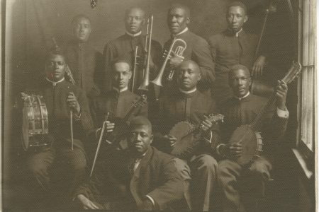 "Piron Williams Band: Clarence Williams seated in front; behind him from left to right are Ernest Trepagnier, drums; Armand Piron, violin; Tom Benton, banjo; Johnny St. Cyr, banjo; standing in the back, from left to right, are Jimmy Noone, clarinet; William ""Baba"" Ridgley, trombone; Oscar Celestin, cornet; and John Lindsay, bass."