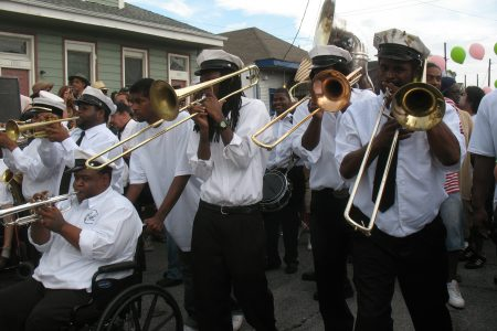 "Members of the Hot 8 Brass Band, including Terrell ""Burger"" Batiste in wheelchair at left and Keith ""Wolf"" Anderson at far right play in traditional black and white uniforms for the Black Men of Labor Social Aid & Pleasure Club second line parade in 2009."