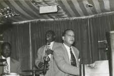 Members of the Smilin' Joe Blues Trio - Alonzo Stewart, Teddy Purnell, and Johnny Fernandez playing the piano - during a performance at the Famous Door nightclub, circa 1954.