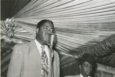 Alonzo Stewart singing into the microphone in front of Smilin' Joe on guitar at the Famous Door nightclub, circa 1954.