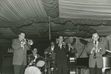 Mike Lala and His Band, including Mike Lala on trumpet, Joe Capraro on guitar, and Bill Bourgeois on clarinet, perform at the Famous Door.