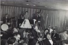 Louis Prima plays trumpet on the floor while Keely Smith watches impassively from the stage at the Sahara in Las Vegas. They ended each show with