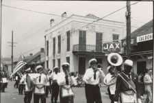 A brass band parading past the Caldonia Inn, sometime between 1952 and 1964. The Caldonia was on a busy second line route in Treme.