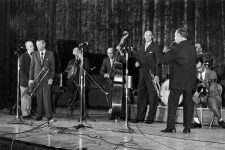 Kid Ory, Emanuel Sayles, Ed Garland, Thomas Jefferson, Raymond Burke, Freddy Kohlman, and Danny Barker at the Municipal Auditorium as part of the 1971 New Orleans Jazz & Heritage Festival.